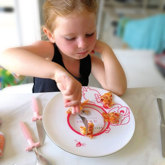 Anna découvre la carte au fond de son assiette.